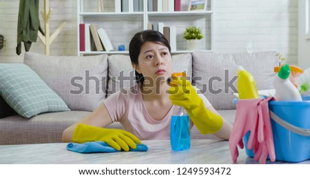 Asian unhappy woman is boring to clean a house. wife is wiping dust using a spray and cloth while cleaning on the table. young lady indoors looking outside view of the sunny urban from home. #1249593472