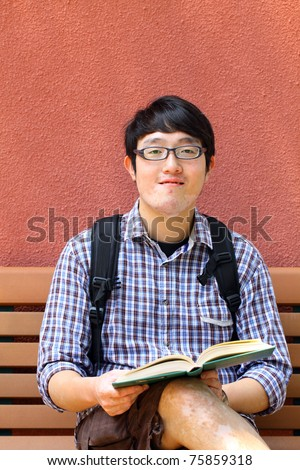 Asian university boy. He is reading book on campus.