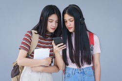 Asian university students chating, talking in university campus. Female university students talking, studying and exchanging together in university campus. Education and life style concept.