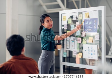 asian ux developer and ui designer presenting mobile app interface design on whiteboard in meeting at modern office.Creative digital development mobile app agency.digital transformation