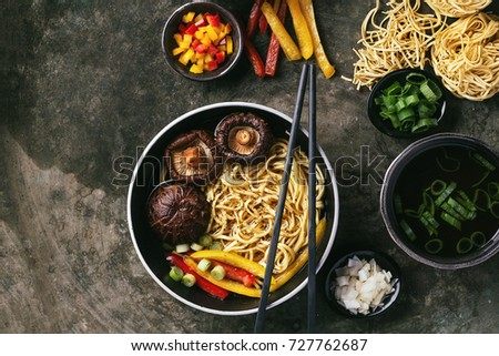 Asian vegan noodles with shiitake mushrooms, bell pepper and scallions served in a black bowl with vegetable. Top View #727762687