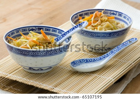 Asian vegetable soup from carrots, field garlic, sprouts and noodles.