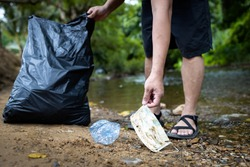 Asian volunteer is picking up trash waste rubbish with garbage bag,medical masks of tourists in national park,problem of littering the face mask during its reopening after COVID-19 quarantine