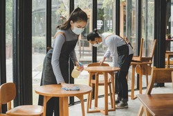 asian waitress staff wearing protection face mask in apron cleaning table with disinfectant spray for protect infection coronavirus (covid-19) in cafe coffee shop restaurant, hotel. new normal concept