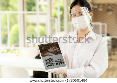 """Asian waitress with face mask and face shield hold digital tablet with QR code for customer to scan for online contactless menu. QR code lead to text""""Online Menu """""""