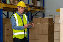 Asian warehouse worker checking packages in storehouse . Logistics , supply chain and warehouse business concept .