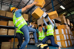 Asian warehouse workers occupational safety and health shocked someone slipped after step on the banana peel and a lot of carton overflowing. thunderstruck in store production.