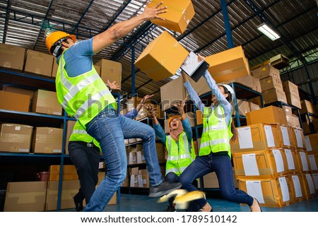 Asian warehouse workers occupational safety and health shocked someone slipped after step on the banana peel and a lot of carton overflowing. thunderstruck in store production. Stock photo ©