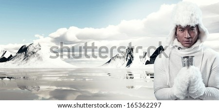 Asian winter fashion man in snow mountain landscape. Wearing white hoody sweater with furry hat and gloves. Holding metal mug.
