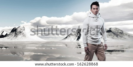 Asian winter fashion man in snow mountain landscape. Wearing white sweater and scarf and brown trousers.