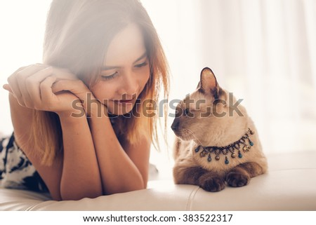 Asian woman and cat laying on sofa with window light.
