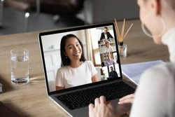 Asian woman and diverse colleagues taking part in group videocall laptop screen view over female shoulder sitting at desk working from home. Distant chat, virtual communication, video call app concept