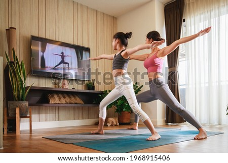 Asian woman and Little girl practicing yoga from yoga online course via smart TV at home. Healthy lifestyle - technology at home. New normal lifestyle. Home Online Stretching Yoga Fitness Exercise.