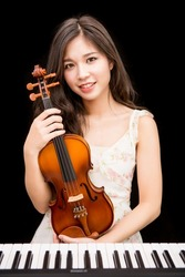 Asian woman and violin isolated over black background
