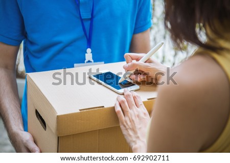 Asian woman appending signature sign on smartphone after accepting receive boxes from delivery man, woman sign on the box, receive delivery concept