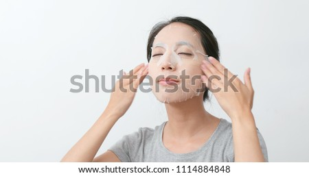 Asian Woman apply paper mask on face