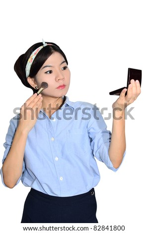 Asian woman applying make up on white background