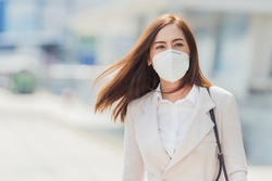 Asian woman are going to work.She is wearing a mask N95. To prevent dust, pm 2.5
