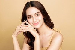 Asian woman are happy with perfect clean healthy skin and beautiful long brown hair. Cute female model clean fresh skin . Expressive facial expressions. Cosmetology concept.