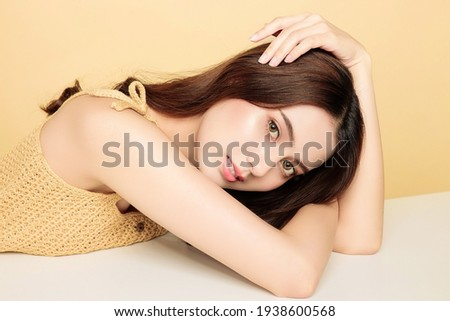 Asian woman are happy with perfect clean healthy skin and beautiful long brown hair. Cute female model clean fresh skin . Expressive facial expressions. Cosmetology concept. Girl beauty face care.