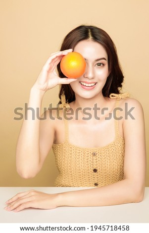 Asian woman are happy with perfect clean healthy skin and beautiful long brown hair. Cute female model clean fresh skin is holding an orange in her hand. Expressive facial expressions. Cosmetology. Zdjęcia stock ©