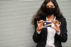 Asian woman at formal wear and black protect face mask hold Marshall Islands flag at hand against gray background. Coronavirus at country concept.