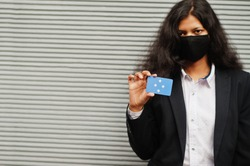 Asian woman at formal wear and black protect face mask hold Micronesia flag at hand against gray background. Coronavirus at country concept.