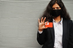 Asian woman at formal wear and black protect face mask hold Tonga flag at hand against gray background. Coronavirus at country concept.