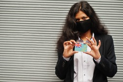 Asian woman at formal wear and black protect face mask hold Tuvalu flag at hand against gray background. Coronavirus at country concept.