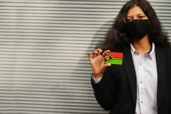 Asian woman at formal wear and black protect face mask hold Vanuatu flag at hand against gray background. Coronavirus at country concept.