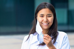 Asian woman, attractive ethnic girl takes off the medical mask from her face, happy with a smile looks at the camera. in a white shirt outside the business center.