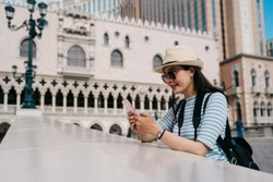asian woman backpacker standing above river canal with tall historic castle buildings in background. smiling girl tourist using cellphone texting message and chatting with friends online on bridge