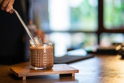 Asian woman barista make iced chocolate with froth milk in the glass on counter. Female coffee shop waitress employee prepare cold drink for customer at cafe. Small business coffee shop owner concept