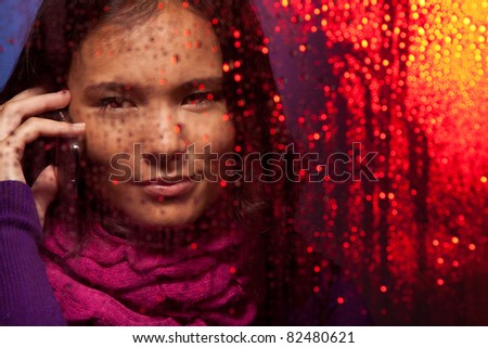 Asian woman behind the glass in rainy weather calling on phone with city light reflecting - stock photo