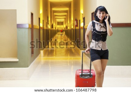 Asian woman chatting on the phone shot in a 5 stars hotel aisle