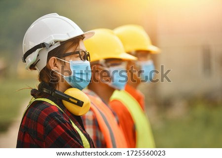 Asian woman civil engineer paper plan building architect wearing white safety helmet look at contruction site.Female foreman in a construction helmet, facemask,