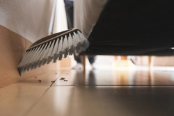 Asian woman cleaning and sweeping dust the floor under the sofa with a broom in the living room. Woman doing chores at home. Housekeeping concept.