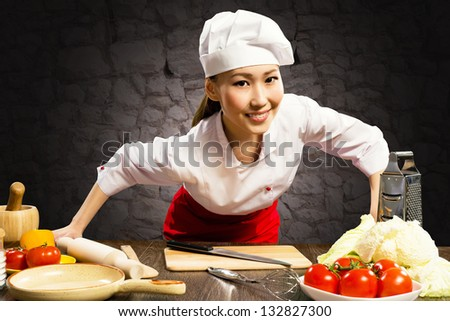 Asian woman cook leaned over the table and looking into the camera