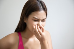 asian woman covering her nose for bad smell, concept of stink thing, bad breath, unpleasant smell, rotten food, odor, body bad smell; young adult southeast asian woman model