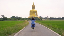 Asian woman cycling a bicycle near the Giant Golden Buddha in Wat Muang in Ang Thong district with paddy rice field near Bangkok. Urban town city, Thailand in travel holiday vacation concept. People