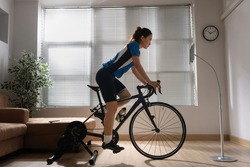 Asian woman cyclist. She is exercising in the home.By cycling on the trainer and play online bike games.She stood up spinning