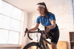 Asian woman cyclist. She is exercising in the house.By cycling on the trainer and play online bike games