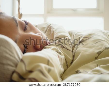 Asian woman deep sleeping on the bed.