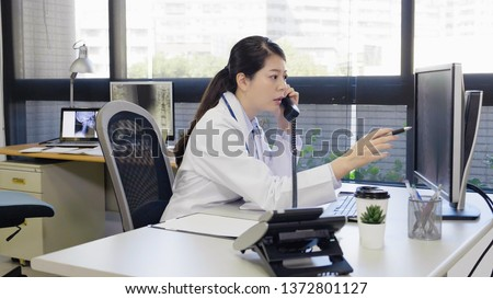 asian woman doctor sitting at desk in front of computer and talking on telephone with a patient telemedicine health hotline consultation. young female medical staff using pen pointing screen discuss