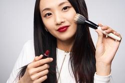 Asian woman doing makeup