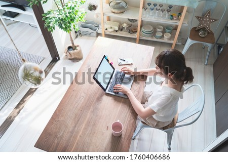 Asian woman doing remote work with laptop at dining table at home