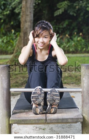 asian woman doing sit ups at a fitness corner with a smile - stock photo