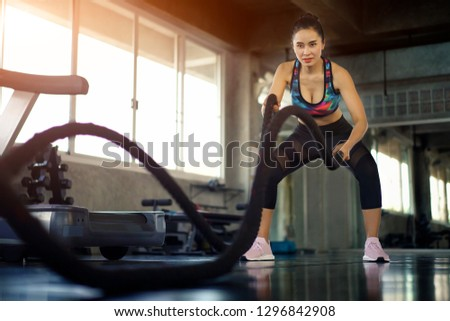 Asian woman doing training battle rope exercise in fitness gym. Female taking weight loss with machine aerobic for slim and firm health. Healthy sport cardio strong.