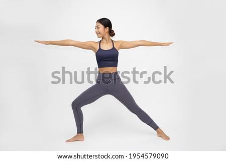Asian woman doing yoga practices Ashtanga Vinyasa Yoga asana Virabhadrasana 2 or warrior pose 2 isolated on white background Photo stock ©