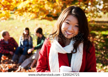 Asian woman drinking a warm drink in the fall